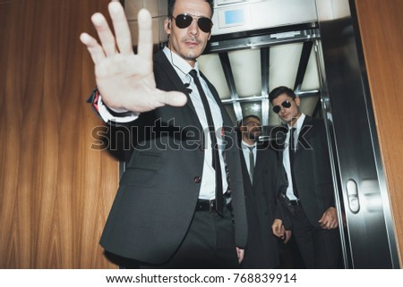 bodyguard obstructing paparazzi when celebrity going into elevator
