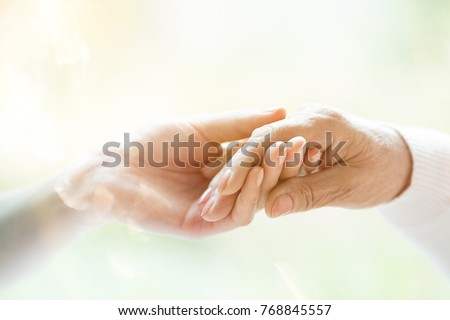 Close-up of young person's hand holding elderly person's hand as sign of caring for seniors #768845557