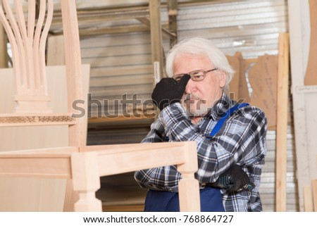 Serious furniture designer carefully polishes the chair frame, which he is busy manufacturing in his woodwork workshop, with shelves of wooden objects and patterns behind him #768864727
