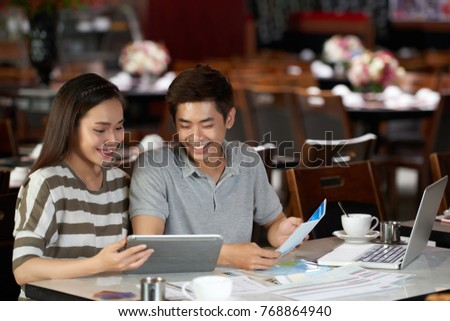Planning trip to Europe: cheerful young couple sitting at spacious cafe while booking hotel and buying airline tickets online #768864940