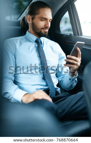 Young Successful Man Working On Phone Sitting In Car. Portrait Of Handsome Smiling Businessman In Formal Clothes Using Phone Riding To Work On Back Seat Of Luxury Business Car.  High Quality Image. #768870664