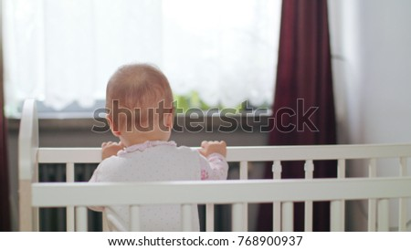 Baby's standing in a white crib at home and playing. Medium shot. #768900937