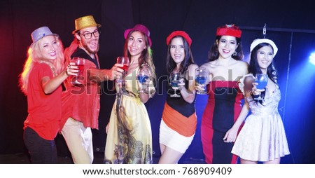 Enjoying amazing party. Group of beautiful young people dancing with champagne flutes and looking happy. new year party, holidays, celebration, nightlife and people concept,smiling friends with glass #768909409