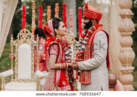 Indian groom dressed in white Sherwani and red hat with stunning bride in red lehenga during the Saptapadi ceremony on Hindu wedding #768926647