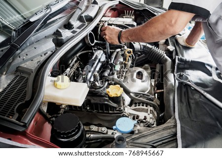 Mechanic with wrench working and repair car engine in car service centre #768945667