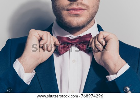 Close up portrait - bearded man ties a bowtie at the collar, correcting red bow on his white shirt over grey background #768974296
