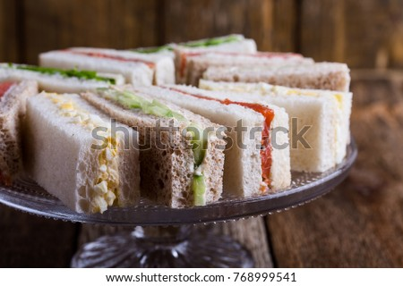 English tea sandwiches on cake over rustic wooden background  Royalty-Free Stock Photo #768999541