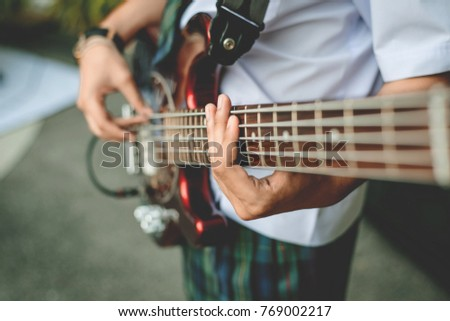 hand of the student playing the bass guitar #769002217