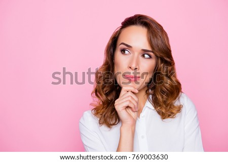 Close up portrait of curious cheerful charming attractive woman with ideal hairdo and make up, she is thinking about the right choice and touching chin, isolated on bright pink background, copyspace Royalty-Free Stock Photo #769003630