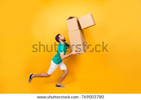 Funny nervous man is carrying his stuff in boxes to the recently bought flat. He is holding cardboard boxes and one is falling down, isolated on yellow background #769003780