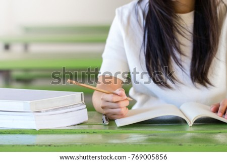Asian woman writting on notebook on the table #769005856