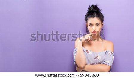 Portrait of a young woman standing against a solid background