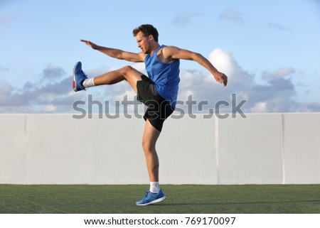 Runner man getting ready to run doing warm-up dynamic leg stretch exercises routine, Male athlete stretching lower body hamstring muscles before going running outside in summer outdoors. #769170097