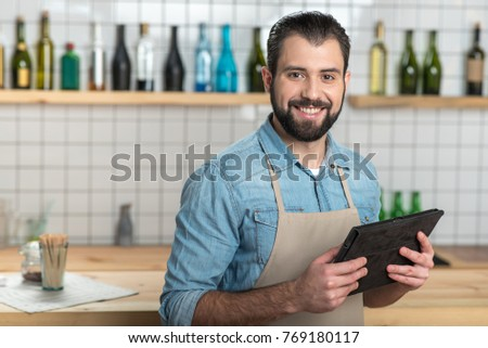 Convenient gadget. Positive emotional bearded waiter looking glad while standing with a modern convenient tablet in his hands and smiling #769180117