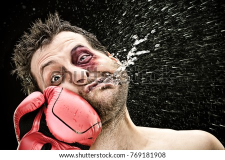 silly boxer man takes a punch in the face isolated on black.funny concept portrait Royalty-Free Stock Photo #769181908