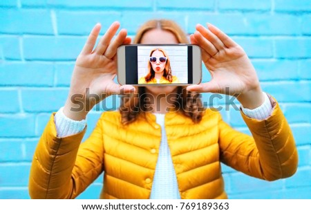 Closeup woman takes picture self portrait on smartphone on blue background