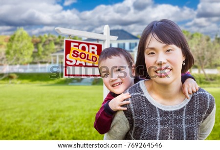 Chinese Mother and Mixed Race Child In Front of Custom House and Sold For Sale Real Estate Sign.