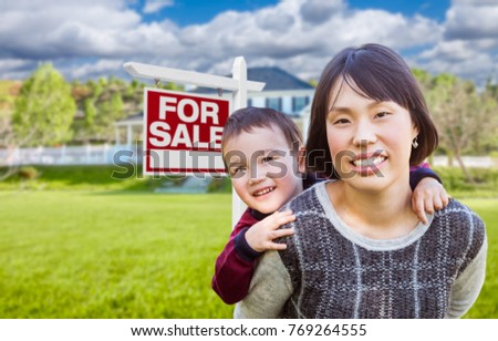 Chinese Mother and Mixed Race Child In Front of Custom House and For Sale Real Estate Sign.