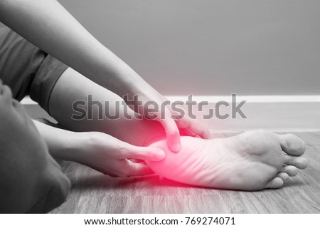 Female foot heel pain with red spot, plantar fasciitis Royalty-Free Stock Photo #769274071
