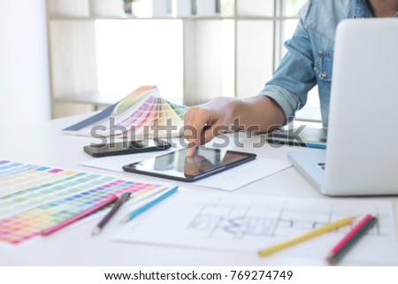 Color samples, colour chart, swatch sample, Graphic designer being selecting Color table and graphics tablet, pen at workplace with work example on wooden desk. #769274749