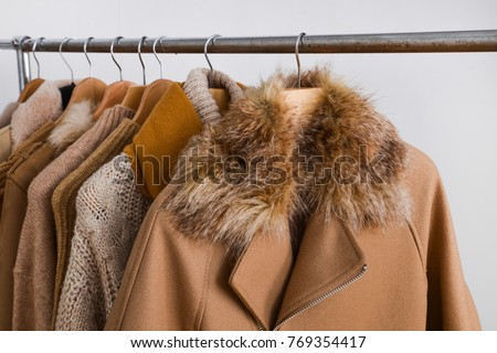 Row of women leather coat and jacket with sweater on hangers isolated  #769354417