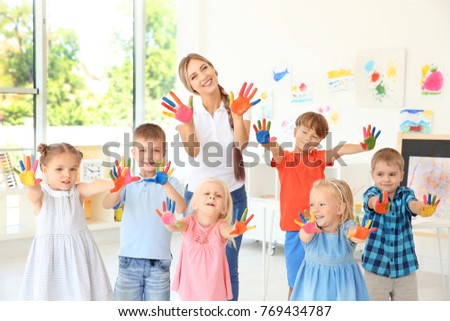 Children and teacher with hands in paint at art lesson Royalty-Free Stock Photo #769434787