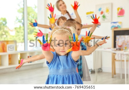 Children and teacher with hands in paint at art lesson