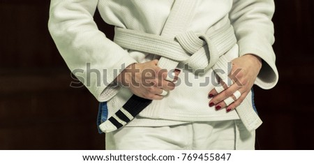 A girl in a kimono kneads before training in judo and jujitsu Royalty-Free Stock Photo #769455847