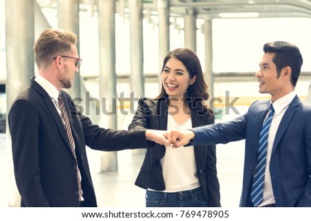?Young businessman and businesswoman making a fist bump on modern building background. Business people wear suit do a fist pump together after good deal. Business success and teamwork concept. #769478905