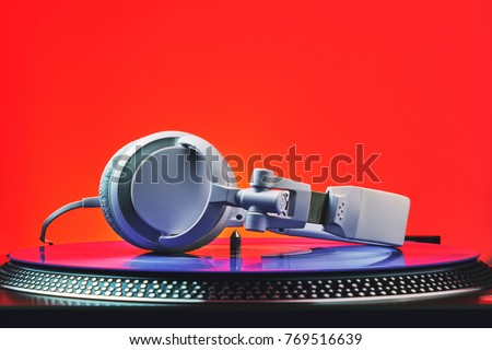 Player turntable vinyl records and white headphones in red light. Equipment for the disc jockey. Sound technology for DJ to mix and play music. Violet vinyl plate. Vinyl turntable in red light Royalty-Free Stock Photo #769516639