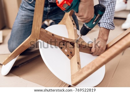 The man handyman is engaged in assembling the chair. The repairman is engaged in mending the chair. #769522819