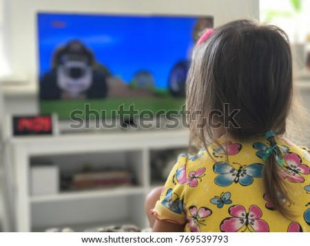 little girl baby sitting on sofa at home and watching big TV with cartoons