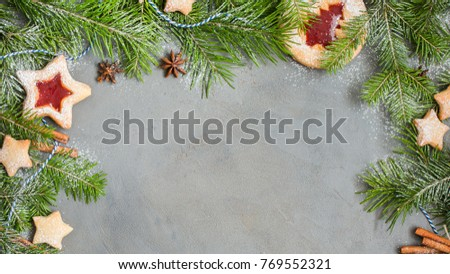 Ginger homemade cookies with strawberry jam on gray concrete background with Christmas tree. Winter holidays concept. Flat lay, top view. Xmas Border - horizontal banner. Web size.  #769552321