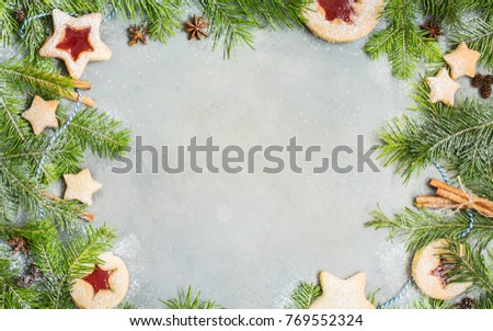 Ginger homemade cookies with strawberry jam on gray concrete background with Christmas tree. Winter holidays concept. Flat lay, top view. Xmas Border - horizontal banner. Web size.  #769552324