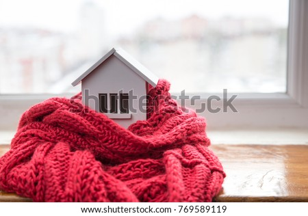 house in winter - heating system concept and cold snowy weather with model of a house wearing a knitted cap Royalty-Free Stock Photo #769589119