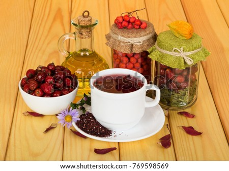 Stocks vitamin berries in banks, oil and drink from rose hips, on background of beige wooden table #769598569