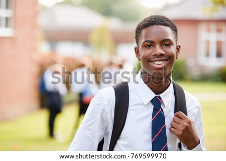 Portrait Of Male Teenage Student In Uniform Outside Buildings Royalty-Free Stock Photo #769599970