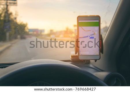 The map on the phone in the background of the dashboard and street . White mobile phone with map gps navigation fixed in the mounting. copy space. #769668427