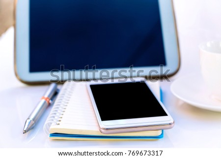 Tablet with a cup and smartphone on the white table.  A lifestyle of the new generation. with copy space for text. focused on smartphone. #769673317