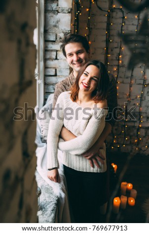 A guy with a girl is celebrating Christmas. A loving couple enjoys each other on New Year's Eve in a cozy home environment. New Year's love story. #769677913
