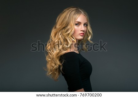 Curly long hair blonde young model. Beauty girl with curly perfect hairstyle #769700200