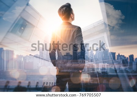 The double exposure image of the business man standing back during sunrise overlay with cityscape image. The concept of modern life, business, city life and internet of things. #769705507