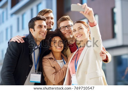 business, education and corporate concept - international group of people with conference badges and smartphone taking selfie on city street #769710547