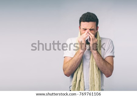 studio picture from a young man with handkerchief. Sick guy isolated has runny nose. man makes a cure for the common cold.Nerd is wearing glasses. Royalty-Free Stock Photo #769761106