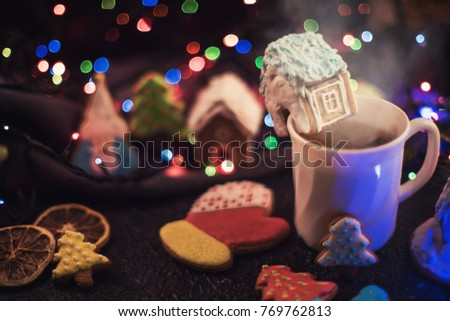 Christmas cookies and cup of tea on dark color bokeh lights background #769762813