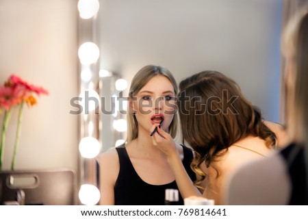 Makeup artist applies lipstick to attractive blonde girl at the mirror with lamps in the beauty studio. #769814641