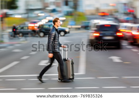 motion blur picture of a businessman with trolley bag who crosses the street #769835326