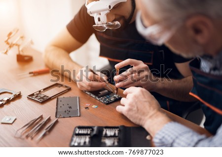Elderly and young men repair a mobile phone together. They work in a repair shop. They use different tools. They are repair specialists. #769877023