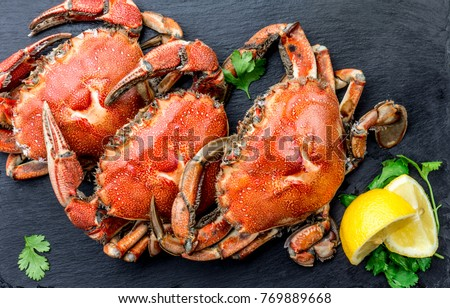 Cooked crabs on black plate served with white wine, black slate background, top view. #769889668