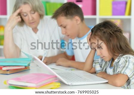 granny with grandchildren doing homework #769905025